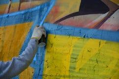 Een hand met een aërosol die een nieuwe graffiti op de muur trekt stock afbeeldingen