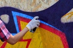 Een hand met een aërosol die een nieuwe graffiti op de muur trekt royalty-vrije stock afbeeldingen
