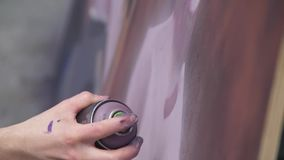 Een hand met een aërosol die een nieuwe graffiti op de muur trekt Foto van het proces om een graffiti op houten te trekken stock video