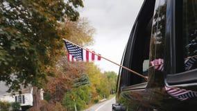 Een hand met een Amerikaanse vlag kijkt uit het venster van een reizende auto langzame geanimeerde video stock footage