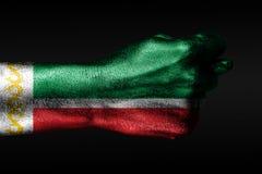 Een hand met een geschilderde vlag van Tchetcheni? toont fig., een teken van agressie, meningsverschil, een geschil op een donker royalty-vrije stock afbeeldingen