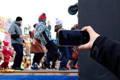 Een hand met een smartphone Het schieten van de Russische vakantie stock fotografie