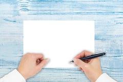 Een hand schrijft op een document op een houten lijst Maak nota's, maak plannen, schrijf, trek Hoogste mening met exemplaarruimte stock foto's