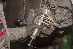 Een hand technische specialist die het remsysteem van de moderne auto herstellen stock afbeelding