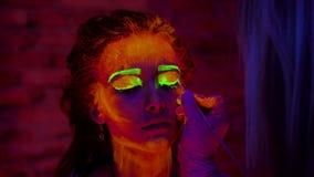 Een hand van kunstenaar die een gezicht van mooi meisje met gloeiende verf met borstel schilderen Mooie vrouw met binnen het gloe stock videobeelden