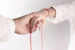 Een hand van paar raakt elkaar Het Geloof van rode draad brengt lot royalty-vrije stock afbeeldingen
