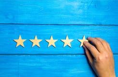 Een hand zet de vijfde houten ster op een blauwe achtergrond De criticus plaatst de kwaliteitsclassificatie Vijf sterren, het hoo royalty-vrije stock foto