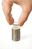 Een hand zet een muntstuk over een stapel van geld Stock Fotografie
