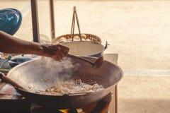 Een handchef-kok maakt Gebraden rijststokken met garnalen in straatvoedsel stock afbeeldingen