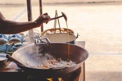 Een handchef-kok maakt Gebraden rijststokken met garnalen in straatvoedsel royalty-vrije stock foto's