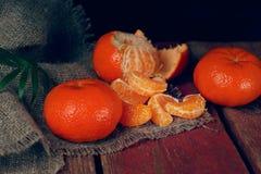 Een handvol van mandarin ligt op een houten lijst, worden wat schoongemaakt en in plakken verdeeld stock fotografie