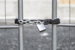 Een hangslot die de poort beveiligen stock afbeeldingen