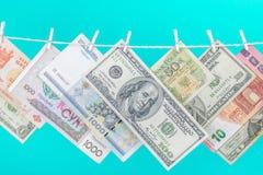 EEN hangt de dollarrekeningen op een kabel met houten die wasknijper op blauwe achtergrond wordt ge?soleerd royalty-vrije stock afbeeldingen