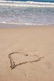 Een hart op zandig strand stock afbeeldingen