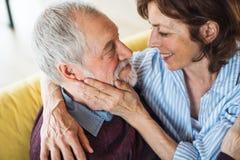 Een hartelijk hoger paar in liefdezitting op bank binnen thuis royalty-vrije stock fotografie