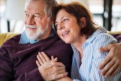 Een hartelijk hoger paar in liefdezitting op bank binnen thuis stock fotografie