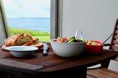 Een hartelijke gezonde maaltijd met eigengemaakt vers gebakken brood, de verse groentesalade en wat kip stoven, in openlucht gedi stock fotografie
