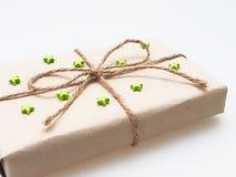 Een heden of giftvakje door ruw bruin gerecycleerd die document wordt en met bruine hennepkabel als lint met groene rubberster wo Royalty-vrije Stock Foto