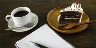 Een heerlijke cake met een koffie en het zakboekje Stock Foto