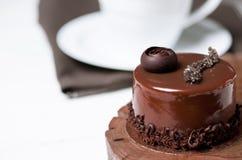 Een heerlijke chocoladecake met chocoladestukken ligt op een houten tribune naast een witte kop, die zich op een witte lijst bevi royalty-vrije stock foto
