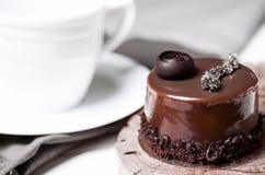 Een heerlijke chocoladecake met chocoladestukken ligt op een houten tribune naast een witte kop, die zich op een witte lijst bevi stock foto's