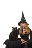 Een heks met een zwarte kat Stock Foto