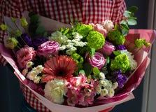 Een helder boeket van verse bloemen in de handen van een jong meisje stock foto