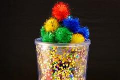 Een helder containerhoogtepunt van kleurrijke, pluizige pom poms royalty-vrije stock foto