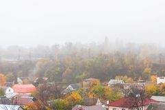 Een helder de herfstlandschap met kleurrijke bomen en daken Stock Fotografie