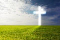 Een helder gloeiend kruis op een groen gebied stock foto