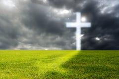 Een helder gloeiend kruis op een groen gebied stock fotografie