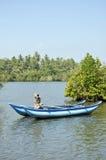 Een heldere blauwe boot liep prachtig op een meer vast Stock Foto