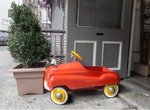Een heldere rode & gele stuk speelgoed brandvrachtwagen komt againsta somber grijs concreet milieu duidelijk uit stock afbeeldingen
