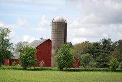Een heldere rode schuur en een silo op een landbouwbedrijf in landelijk Illinois Stock Foto's