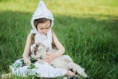 Een herdersmeisje in een witte kleding en een bonnet voedt een geit met koolbladeren stock afbeeldingen