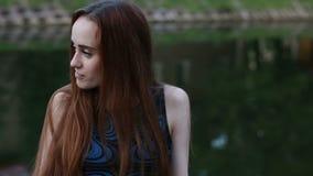 Een herfstportret van een jonge vrouw, die omheining in het park steunt Zij die iets, het vrouwelijke stellen wachten stock video