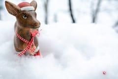 Een hert bevindt zich in een sneeuwafwijking op een achtergrond van bomen stock foto