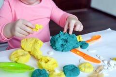 Een 1 het 5 éénjarigenmeisje zit bij een lijst en speelt met een kleurentest, op de lijst lig hulpmiddelen, vormen en deegwaren v stock afbeelding
