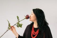 Een het charmeren brunette ruikt een rood toenam Internationale Vrouwen` s Dag Een gift voor geliefd Vrouwen` s geheimen Stock Fotografie
