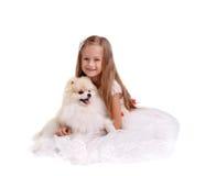 Een het glimlachen jonge damezitting op een grond die op een witte achtergrond wordt geïsoleerd Een meisje met een hond Het conce Royalty-vrije Stock Foto