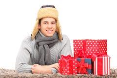 Een het glimlachen kerel met hoed en boorden en dassen die op een tapijt dichtbij prese liggen Stock Foto