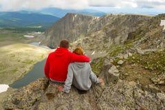 Een het houden van paarzitting op de rand van een rots omhelst vooraan royalty-vrije stock afbeelding