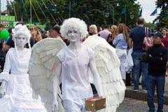 Een het leven standbeeld van een engel loopt onderaan de straat amid mensen, bij de viering van de Dag van Europa stock fotografie