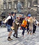 Een het presteren groep bij het de Randfestival die van Edinburgh vliegers op de Koninklijke Mijl uitdelen royalty-vrije stock foto