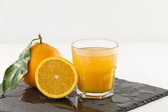 Een het uitnodigen glashoogtepunt van jus d'orange, een halve sinaasappel en gehele met blad op een natte vierkante achtergrond v royalty-vrije stock afbeeldingen