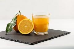 Een het uitnodigen glashoogtepunt van jus d'orange, een halve sinaasappel en gehele met blad op een vierkante leiplaat op witte a stock foto