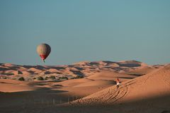 Een hete luchtballon die over de woestijn vliegt stock fotografie
