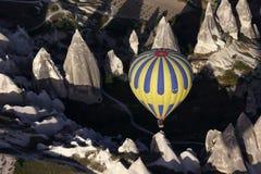 Een hete luchtballon navigeert het manier onderaan Rose Valley bij zonsopgang, dichtbij Goreme in het Cappadocia-gebied van Turki Stock Afbeeldingen