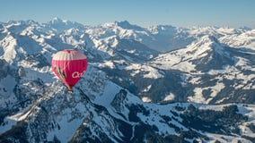 Een hete luchtballon over de sneeuw behandelde tijdens de vlucht hoge berg alpiene pieken van centraal Zwitserland stock afbeeldingen