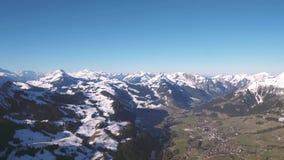 Een hete luchtballon over de sneeuw behandelde tijdens de vlucht hoge berg alpiene pieken van centraal Zwitserland stock footage